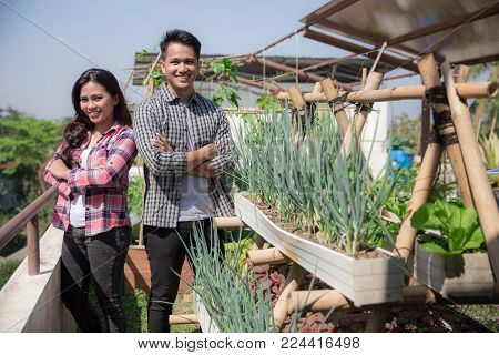 two young people standing proudly in front of their garden. urban farming concept