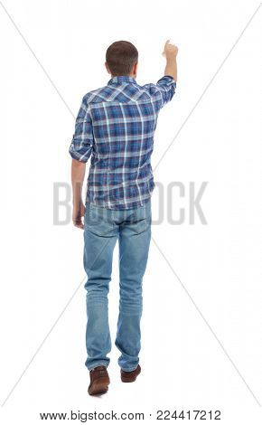 Back view of going  handsome man in jeans pointing. walking young guy . Rear view people collection.  backside view of person.  Isolated over white background. A man in a blue shirt is going to show