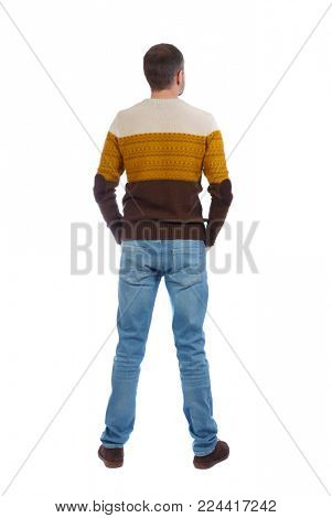 Back view of man in jeans. Standing young guy. Rear view people collection.  backside view of person.  Isolated over white background. A man in a warm sweater stands by putting his hands in his pocke