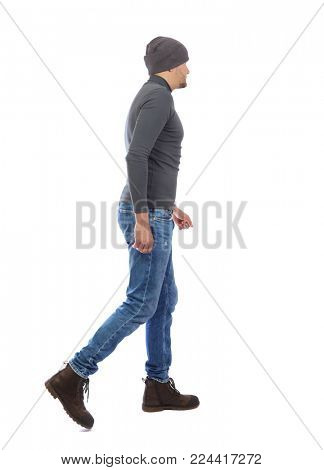 Back view of going  handsome man. walking young guy . Rear view people collection.  backside view of person.  Isolated over white background. A man in a gray sweater and a hat goes by