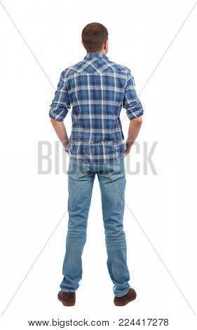 Back view of man in jeans. Standing young guy. Rear view people collection.  backside view of person.  Isolated over white background. A man in a blue shirt stands his back with his hands in his pocke