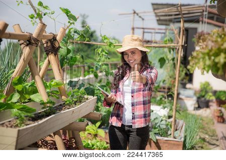 woman showing thumb up while standing in her small farm