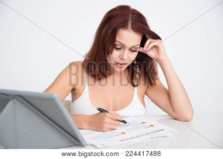 Concentrated female analyst examining report while working at home. Busy young accountant doing paperwork at desk. Analytics concept