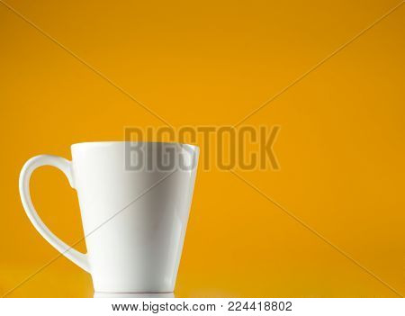 White Cup Isolated on yellow background with copy space .