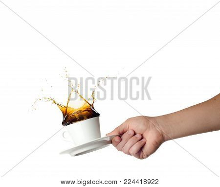 Hand holding cup with splashing coffee isolated on white background