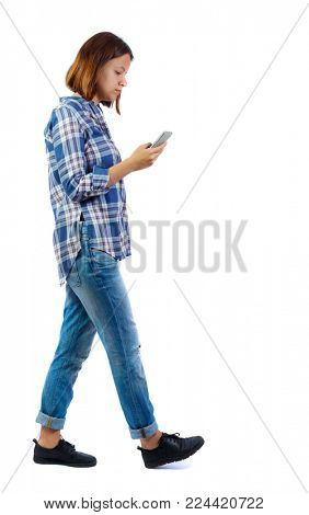 side view of a woman walking with a mobile phone. back view ofgirl in motion.  backside view of person.  Rear view people collection. Isolated over white background. A girl wearing a blue checker