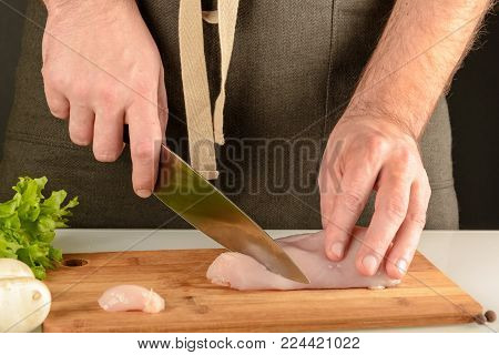 Preparation of healthy food.A man in an apron is cutting meat on a wooden board. Chicken making.