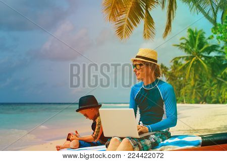 father with laptop, son looking at touch pad on beach, modern technology
