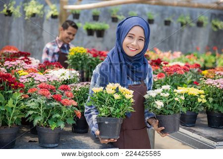 two happy asian male and female florist working in the flower shop