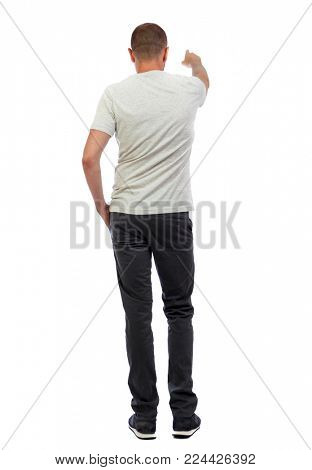 Back view of  pointing young men in  shirt and jeans. Young guy  gesture. Rear view people collection.  backside view of person.  Isolated over white background. A guy in a white T-shirt and trousers