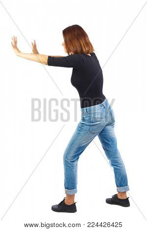 back view of woman pushes wall.  Isolated over white background. Rear view people collection. backside view of person. The girl in a black jacket pushes something in the side.