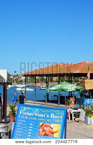 ALVOR, PORTUGAL - JUNE 7, 2017 - Waterfront restaurants with views across the estuary and a menu in the foreground, Alvor, Algarve, Portugal, Europe, June 7, 2017.