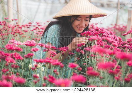 portrait of beautiful asian women sniff on chamomile flowers in the farm