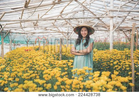 portrait of beautiful asian woman in the flower farm crossed her arm