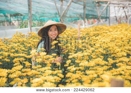 portrait of happy young asian woman in chamomile farm