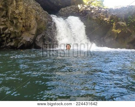 Female caucasian tourist smiling and swimming in water at Togitogiga Waterfall on Upolu Island, Samoa, South Pacific.