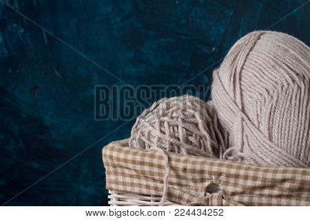 Light Gray Knitting, Yarn In A Basket, Books On A Wooden Table