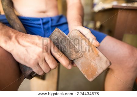 The man sharpens an ax with a sharpener .