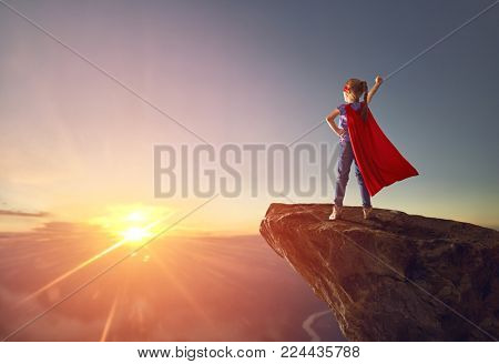 Little kid is playing superhero. Child on the background of sunset sky. Girl power concept