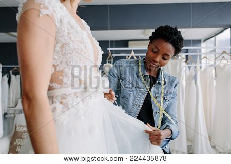 Female fashion designer working in bridal wear store and writing in a diary. Female bridal store owner in her boutique.