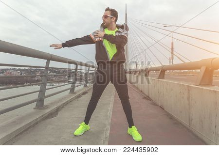Urban jogger stretching on a bridge above the river.