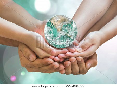 Green globe in family volunteer hands for earth day and CSR with people concept. Elements of this image furnished by NASA.