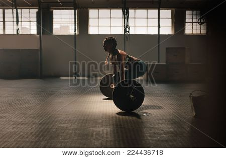 Muscular woman holding gymnastic rings at the gym and looking away. Strong female taking rest after training session.