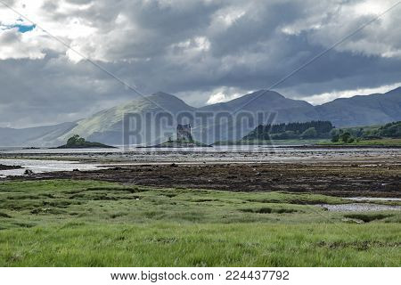 Castle Stalker seen from Jubilee Bridge in Appin with breathtaking view of mountains in the background, Argyl, Scotland