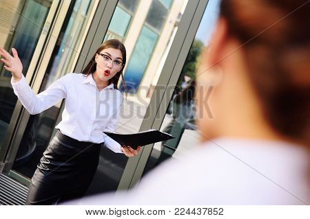 business woman boss scolds and yells at his subordinates on the office background
