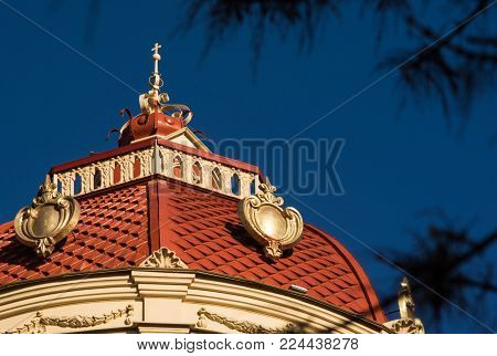 red tile on the roof of the castle tower with a spire in the form of a cross