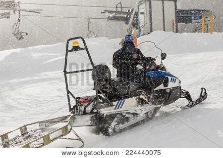 Snowmobile in the Dolomites. All-Terrain Vehicle. Modern Snow-Vehicle. Snowmobile on the ski slope in the Dolomites. Man rides on a snowmobile during a snowfall.