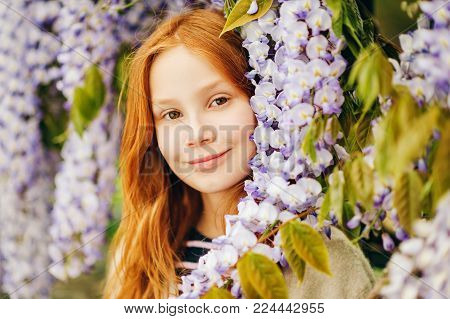 Close up portrait of adorable 9-10 year old red-haired kid girl posing in wisteria