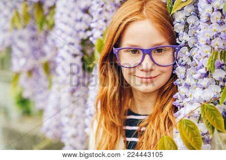 Close up portrait of adorable 9-10 year old red-haired kid girl posing in wisteria wearing purple eyeglasses