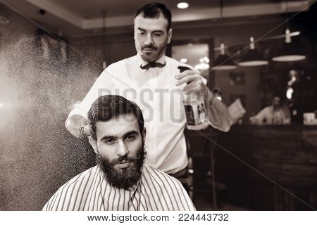 The barber sprinkles on the hair of a young male client of a barber shop with water from a bulb. Haircut, styling beard
