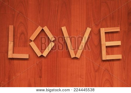 Wooden blocks in shape of word Love on wooden background