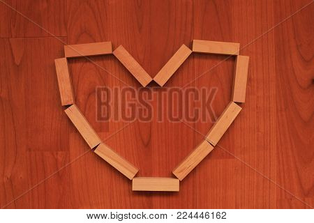 Wooden blocks in shape of Heart on wooden background