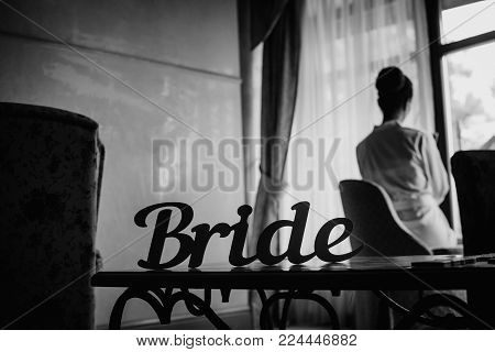 black&white the bride in the morning at the window dreams with a hairdress in a white coat