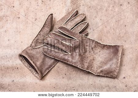 workshop on sewing gloves - top view of new hand-made stitched gloves on original natural leather background