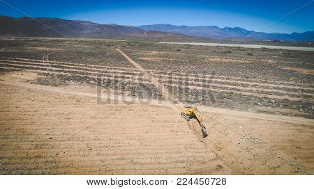 Aerial Photo Of Earth Moving Machinery Front Loader Digging A Trench On A Farm