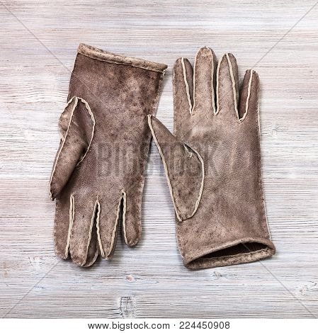 workshop on sewing gloves - top view of pair new hand-made gloves on wooden background