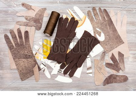 workshop on sewing gloves - top view of various objects for gloves production on wooden background