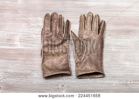 workshop on sewing gloves - top view of new hand-made stitched gloves on wooden background