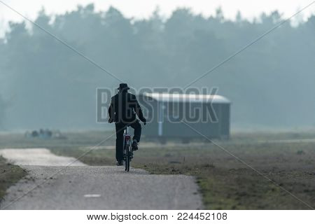 Man in hat cycling on path in misty nature reserve.