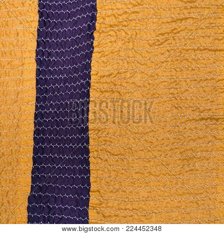 workshop on sewing a patchwork scarf - yellow textile background from stitched strips of silk fabrics