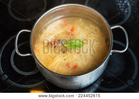 cooking soup - soup from stewed sour cabbage in stockpot on ceramic cooker