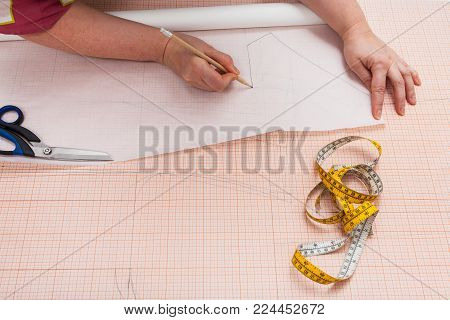 tailor tracing the hand drawn clothing pattern on tracing-paper