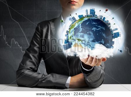 Closeup of businessman in suit keeping in hands Earth globe with buildings and flying balloons. Elements of this image are furnished by NASA.
