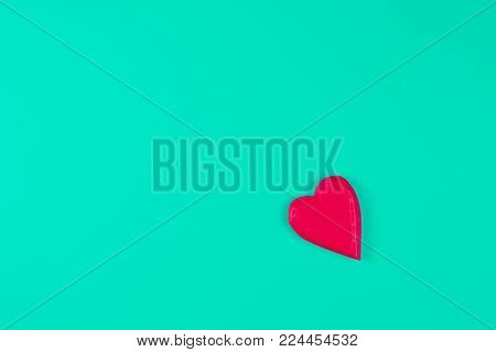 Red wooden heart on turquoise background. Top view