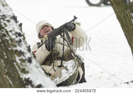 St. Petersburg, Russia - February 23, 2017: German soldier who is furiously shooting back from the automatic machine. Historical reconstruction Second World War.