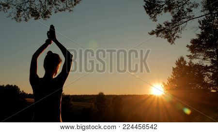 Woman practicing yoga in park at sunset - sun salutation. Sunset light, golden hour. Freedom, health and yoga concept